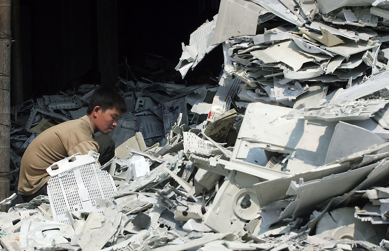 A junk yard worker sorts plastic scraps of old computers and electronic trash in Guiyu, China March 3, 2005. For years, developed countries have been exporting tons of electronic waste to China for inexpensive, labor-intensive recycling and disposal. Since 2000, it's been illegal to import electronic waste into China for this kind of environmentally unsound recycling. But tons of debris are smuggled in with legitimate imports, corruption is common among local officials, and China's appetite for scrap is so enormous that the shipments just keep on coming...