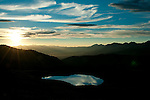 An alpine tarn reflects the evening light as sunset begins to wash over the Gunnison Valley as viewed from Cottonwood Pass near Buena Vista, Colorado.