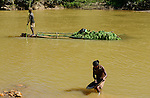MADAGASCAR, region Manajary, town Vohilava, small scale gold mining, women panning for gold at river ANDRANGARANGA, background transport of banana on bamboo float / MADAGASKAR Mananjary, Vohilava, kleingewerblicher Goldabbau, Frauen waschen Gold am Fluss ANDRANGARANGA, Hintergrund Transport von Bananen auf einem Bambus Floss