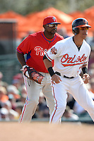 Philadelphia Phillies first baseman Ryan Howard (6) gets ready behind runner Quintin Berry (34) during a spring training game against the Baltimore Orioles on March 7, 2014 at Ed Smith Stadium in Sarasota, Florida.  Baltimore defeated Philadelphia 15-4.  (Mike Janes/Four Seam Images)