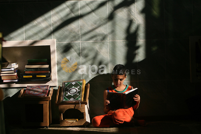 A Palestinian boy reads holy Quran at a mosque in Rafah refugee camp, southern Gaza Strip, during Muslims fasting month of Ramadan, July 29, 2013. Ramadan is the holiest month in the Muslim calendar, during which people refrain from eating, drinking and smoking from sunrise to sunset. Photo by Eyad Al Baba
