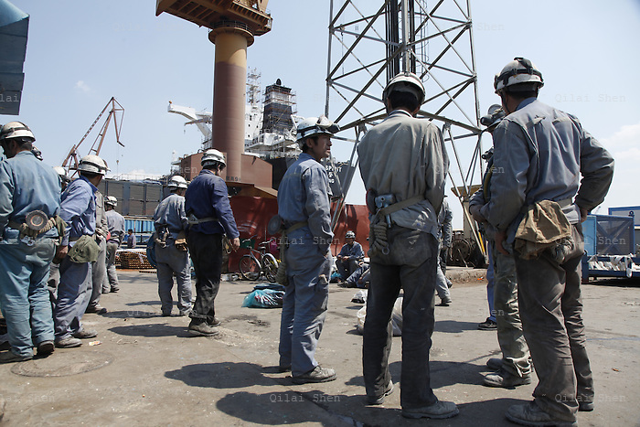 Workers get ready to return to their tasks after lunch break at the Dalian shipyard in Dalian, Liaonin Province, China on 23 April 2011. China's shipping industry is expected to make a strong recovery as over capacity is smaller than expected and China's demand for raw materials needs more ships to transport them.