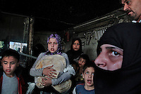 Civilians take shelter inside a welding shop from a fighter jet as it circled around a neighborhood close to an Free Syria Army headquarter in the heart of Aleppo. After dropping four bombs (which killed 7 civilians in an apartment building including a man who burned to death inside his vehicle on the side of the road), the jet switched to its 50 caliber machine gun before leaving the area. .© Javier Manzano