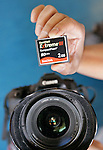 Photographer Stanley Huang, of the Ming Pao Daily News, holds up his SanDisk Compact Flash disk next to his camera in San Jose, Calif., Wednesday, Sept. 17, 2008. A $5.85 billion bid by Samsung Electronics Co. to take over SanDisk Corp., a wounded competitor that also serves as a partner, reflects the turbulence in the market for flash memory, a key ingredient in digital cameras, music players and other devices. (AP Photo/Paul Sakuma)