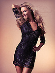 Fashion photo of a young beautiful smiling woman with flying long blond hair wearing a black dress