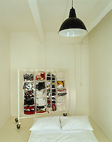 In this small white bedroom, clothes storage on wheels is a flexible solution