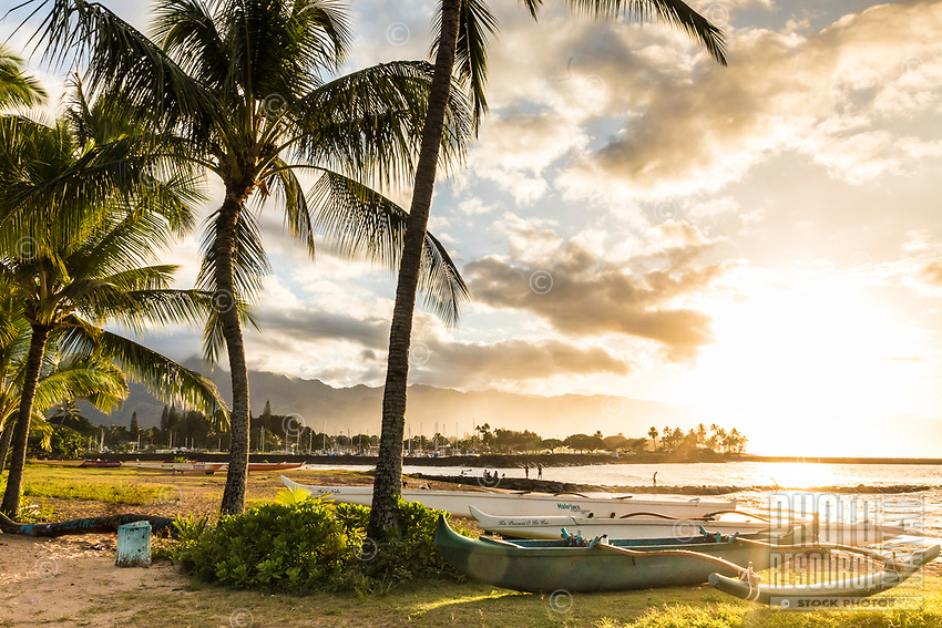 Outrigger canoes at Hale'iwa Beach Park at sunset, with Hale'iwa Small Boat Harbor and Mount Ka'ala in background, North Shore, O'ahu.