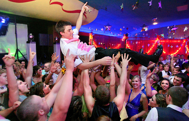 Floating on a sea of hands above joyous faces, Ankeny senior Tom Wignes body surfs the crowded Val Air ballroom floor at the 2008 Ankeny prom.