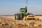 Tractor hoeing crop field for planting. Fresno County, San Joaquin Valley, California, USA