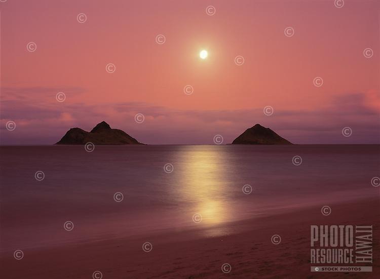 Sunset colors enhance a full moon rising between the Mokulua Islands off of Lanikai Beach, Oahu, Hawaii.
