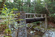 Built in 1923, Memorial Bridge crosses Cold Brook along the Link Trail in Randolph, New Hampshire. This bridge is a memorial to the early Randolph pathmakers. A few of these early trail builders are Charles E. Lowe, Eugene B. Cook, Laban Watson, and William G. Nowell.