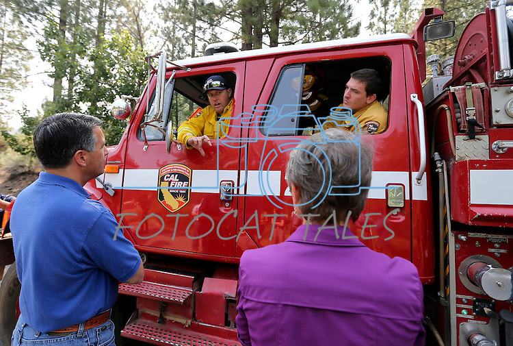 Nevada Gov. Brian Sandoval, left, and U.S. Secretary of the Interior Sally Jewell, right, talk with Cal Fire Capt. Chris Guidice, left, and Firefighter Brandon White in Markleeville, Ca. on Wednesday, June 24, 2015. The lightning-caused Washington fire has grown to nearly 17,000 acres since Friday. <br /> Photo by Cathleen Allison