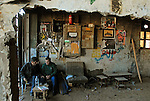 Men sit together at the entrance to a wood workshop in Ramallah, West Bank.