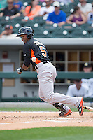 Julio Borbon (5) of the Norfolk Tides tries to outrun the baseball during the game against the Charlotte Knights at BB&T BallPark on June 7, 2015 in Charlotte, North Carolina.  The Tides defeated the Knights 4-1.  (Brian Westerholt/Four Seam Images)