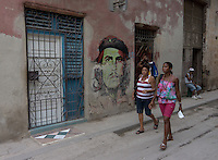 girls passing by a Che guevara graffiti in street scene in Havana Veija,  Cuba