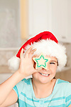 USA, California, Lawndale, Portrait of girl (10-11) wearing santa hat holding cookie