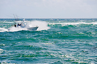 A small fishing boat returning to the Boynton Beach Inlet, Boynton Beach, Florida is challenged by windy conditions and rough seas.