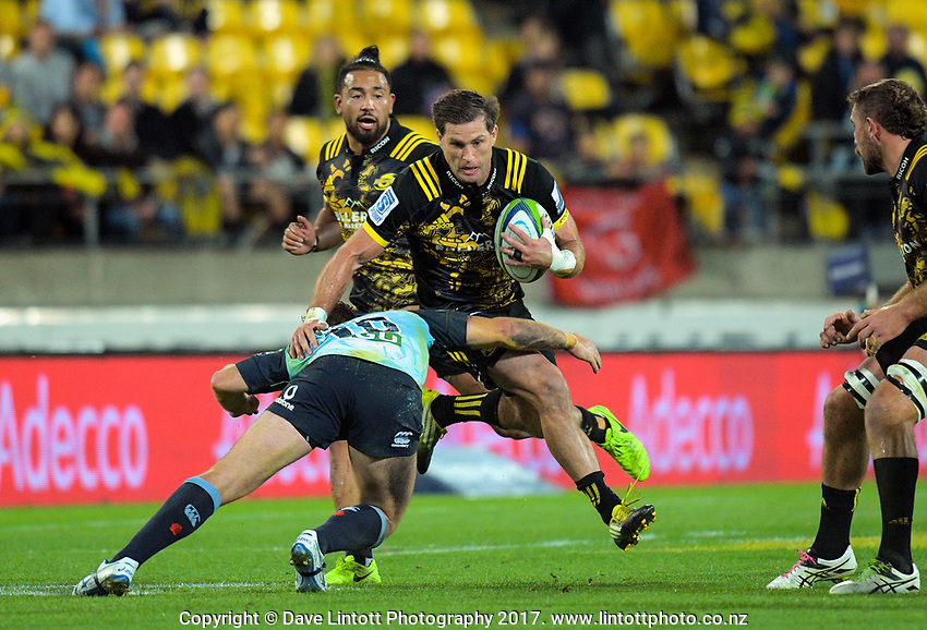 Bernard Foley tackles Cory Jane during the Super Rugby match between the Hurricanes and Waratahs at Westpac Stadium in Wellington, New Zealand on Saturday, 7 April 2017. Photo: Dave Lintott / lintottphoto.co.nz