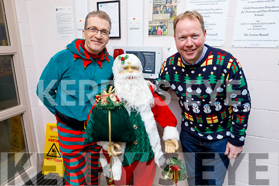 Roger Price and Robbie O'Connell helping Santa Claus at the St Pat's Blennerville Juvenile Christmas party in the school on Friday.