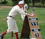 """Belleville Stags outfield scout Bill """"Bean"""" Evans tallies his ace as he scores at home plate in their Saturday August 18 game under the Gateway Arch on the St. Louis riverfront.  You first had to ask permission of the arbiter (the forerunner of the modern-day umpire) to ring the bell (tally your ace). The home-made scoreboard displays the inning and the score. The Stags, Lafayette Cyclone, and the Unions competed in ao build interest in vintage base ball and were hosted on the site by the Federal Park Service, which had information booths and handouts for interested people.  About 150 people around the perimeter of the makeshift field watched all or part of the three games the teams played."""