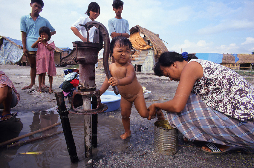 VOLCANO AFTERMATH, Philippines.  Mother washing her daughter from water  standpipe, tent city for refugees. Central Luzon, Mount Pinatubo volcano erupted in 1991  and caused massive destruction of urban and rural landscape. Many indigenous  Aeta and Igorot people were displaced. White volcanic  ashes settled and disfigured the landscape.   Many  live in ramshackle shelters, in  refugee camps and settlements, living on humanitarian aid.