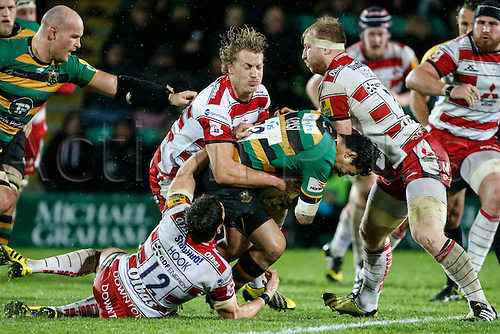 27.11.2015.  Franklin's Gardens, Northampton, England. Aviva Premiership. Northampton Saints versus Gloucester. George Pisi of Northampton Saints is tackled by James Hook, Billy Twelvetrees and Matt Kvesic of Gloucester Rugby.