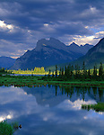 Banff National Park, Canada    <br /> Mount Rundle reflecting on Vermillion Lakes with sun breaks lighting the distant wetland trees