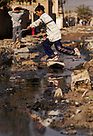 A boy in the Taric district of the Sadr City neighborhood in Baghdad picks his way through raw sewage filling the street. The sewage seeps into leaky water pipes, contaminating the area's drinking supply.