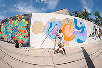 Street artists Cey Adams at work at the Welling Court Mural Project in the Astoria neighborhood of Queens in New York on Saturday, June 13, 2015. The annual neighborhood event decorates walls in this industrial part of Astoria. The project is crowd-funded and emerging street artists work side by side with established stars.  (© Richard B. Levine)