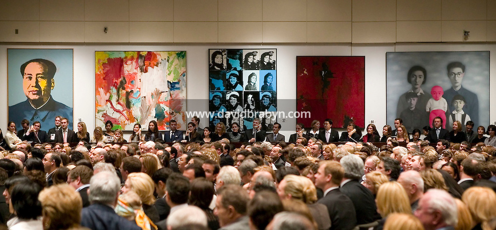 14 November 2006 - New York City, NY - View of the auction room with (LtoR) Andy Warhol's Mao, Willem de Kooning's Untitled XXV, Andy Warhol's Sixteen Jackies, Clyfford Still's 1947-R-NO.1 and Zhang Xiaogang's A Big Family Series No.16 stand on display during a sale of Post-War and Contemporary Art at the Christie?s auction house in New York City, USA, 14 November 2006. The sale reached a total of $239,704,000.