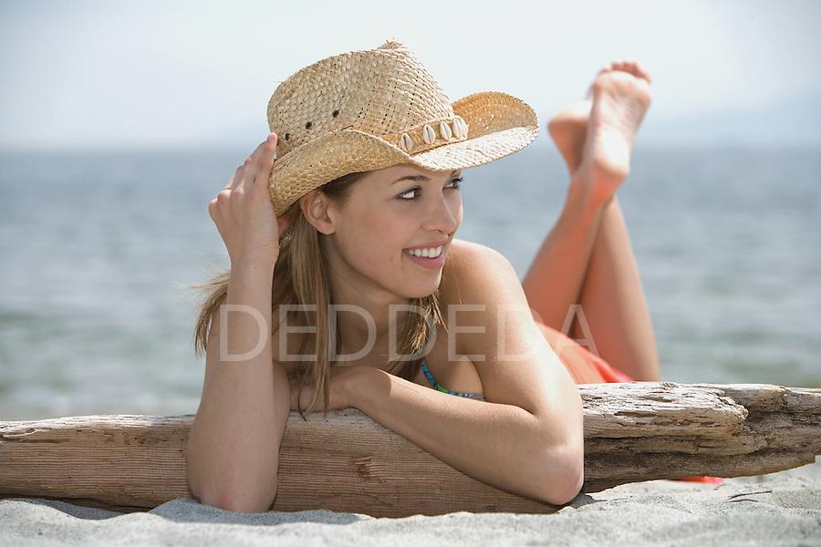 A beautiful young woman wearing a bikini and straw cowboy hat at Cadboro Bay Beach in Victoria, BC, British Columbia, Canada.