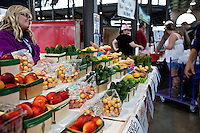 A woman sells vegetables at her stall in Detroit Eastern Farmers market in Detroit (Mi) Saturday June 8, 2013. The largest open-air flowerbed market in the United States, the Eastern Market is a historic commercial district in Detroit, Michigan.