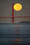While the full moon slowly sets behind the Golden Gate Bridge it left a moon beam trail on the San Francisco bay pointing to Treasure Island, California.