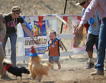 Karla Burrell and David Baxley guide 2-year-old Nekolas Bowers in the chicken race during the 54th International Camel Race in Virginia City, Nev., on Friday, Sept. 6, 2013.  <br /> Photo by Cathleen Allison