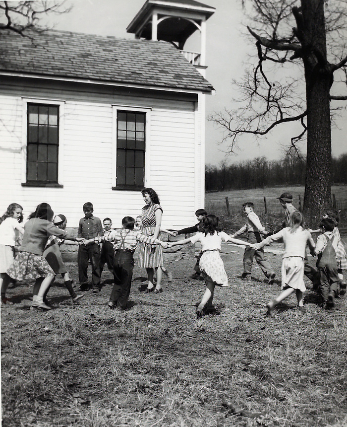 Children and teacher playing in schoolyard. 1950's.<br />
