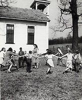 Children and teacher playing in schoolyard. 1950's.<br />