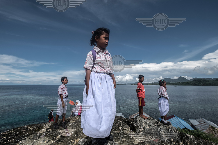 Bajau schoolchildren look out to sea from the top of a rock in Kabalutan village, during a break between classes. Until recently few Bajau received any kind of formal education. (Photo: Aurélie Marrier d'Unienville)