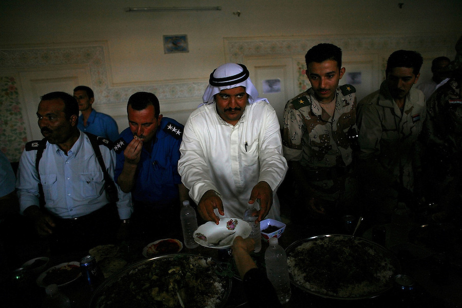 During an event held by Iraqi policemen to host their Iraqi Army counterparts  - representatives of the three dominant Iraqi power groups in a a newly tamed Ramadi - police, tribal leaders, and the Iraqi Army - stand side by side as they share lunch together on Wednesday May 23, 2007. The police - a local Sunni force - and the Army - primarily a Shiite force from Baghdad and the Iraqi south - are overtly distrustful of each other.