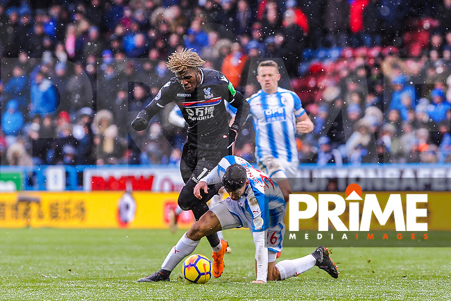 Huddersfield Town's defender Christopher Schindler (26) fouls Crystal Palace's midfielder Wilfried Zaha (11) during the EPL - Premier League match between Huddersfield Town and Crystal Palace at the John Smith's Stadium, Huddersfield, England on 17 March 2018. Photo by Stephen Buckley / PRiME Media Images.