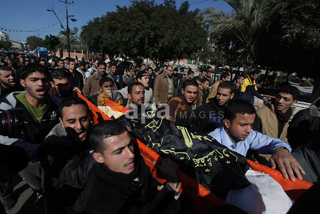 "Palestinian mourners carry the body of an Islamic Jihad militant who was killed by in what medics and his family said was an Israeli drone strike mourn during his funeral in Gaza City on January 8, 2014. Mohammed al-Ijlah, 32, was ""killed by an Israeli drone in Shejaiyeh,"" said Ashraf al-Qudra, spokesman for the Hamas-run health ministry, referring to a district near the Israeli border with Gaza. Israeli military denied carrying out any strike on Gaza, with a spokeswoman saying she was unaware of any such incidents in the area. Photo by Ashraf Amra"