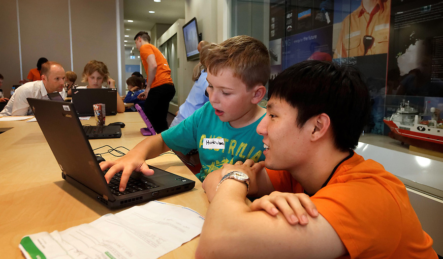 CoderDoJo, a volunteer led coding club for kids where they learn to code. One of the WA chapters is held at Woodsides' Perth HQ. Patrick Bae, a graduate IT analyst at Woodside with Hunter Jones (9). photo by Trevor Collens 8/12/2016