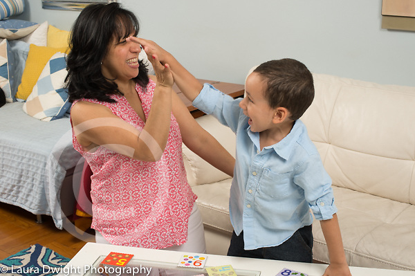 3 year old boy giving mother high five in congratulations after he found pairs in memory game