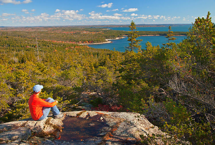 A woman sits atop Schoodic Head along the East Trail on the Schoodic Peninsula, Acadia National Park, Maine, USA