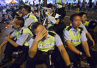 Tired Hong Kong police officers are seen before they lost control of the area, and thus ceding it back to the protesters, who had only just lost it to the police hours earlier in a pre-dawn raid, Mong Kok, Kowloon, Hong Kong, China, 18 October 2014.