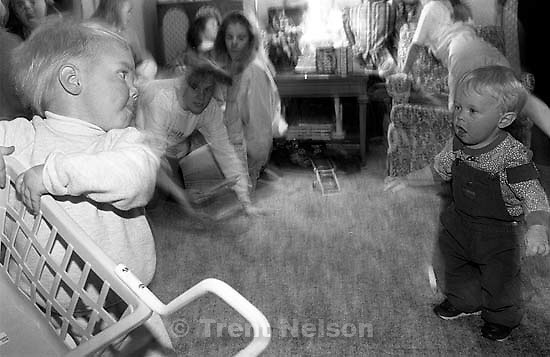 Rebecca Clark pulls toy shopping cart away from her cousin at family Christmas party.<br />