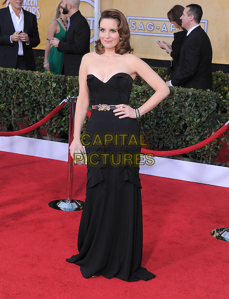 Tina Fey (wearing Oscar de la Renta).Arrivals at the 19th Annual Screen Actors Guild Awards at the Shrine Auditorium in Los Angeles, California, USA..27th January 2013.SAG SAGs full length dress black silver belt clutch bag strapless hand on hip.CAP/DVS.©DVS/Capital Pictures.
