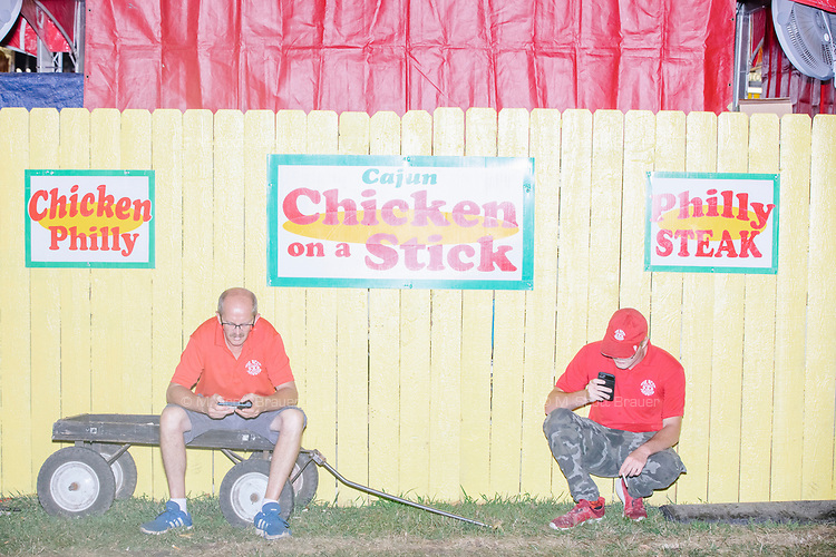 Fair workers take a break behind a food vendor booth at the Iowa State Fair in Des, Moines, Iowa, on Sun., Aug. 11, 2019.