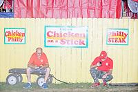 Fair workers take a break behind a food vendor booth at the Iowa State Fair in Des, Moines, Iowa, on Sun., Aug. 11, 2019.