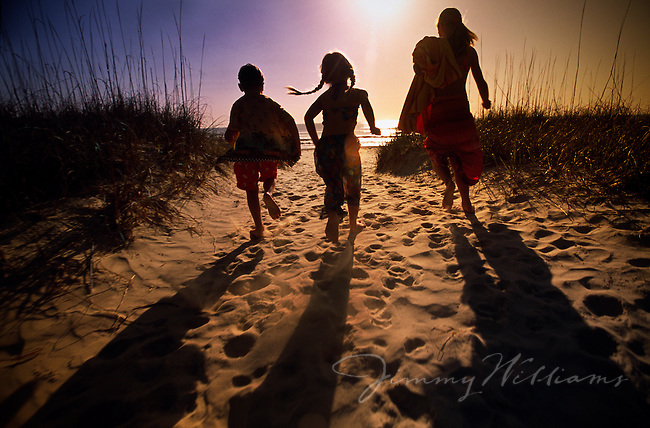 Three Kids Run Down To The Beach At Sunset