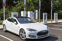 A Tesla Model S gets a charge from a Tesla supercharger charging station at a highway rest stop.
